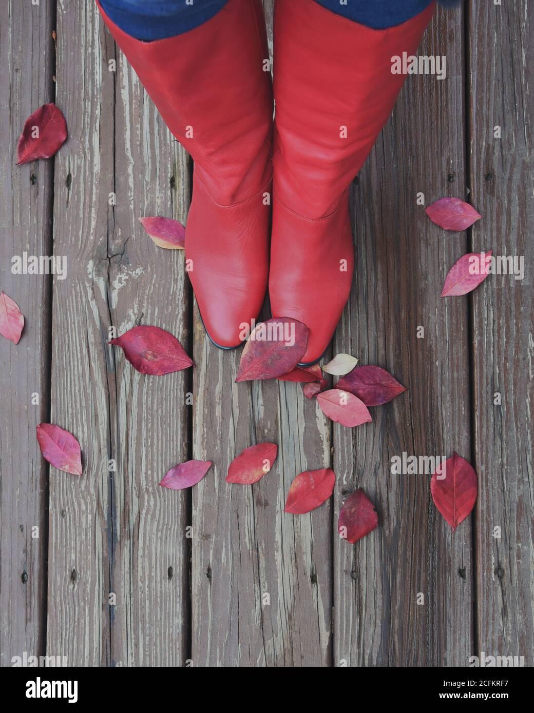 Une paire de bottes rouges pour femmes regarde vers le bas sur les feuilles d'automne contre un plancher de bois pour un concept saisonnier. Banque D'Images