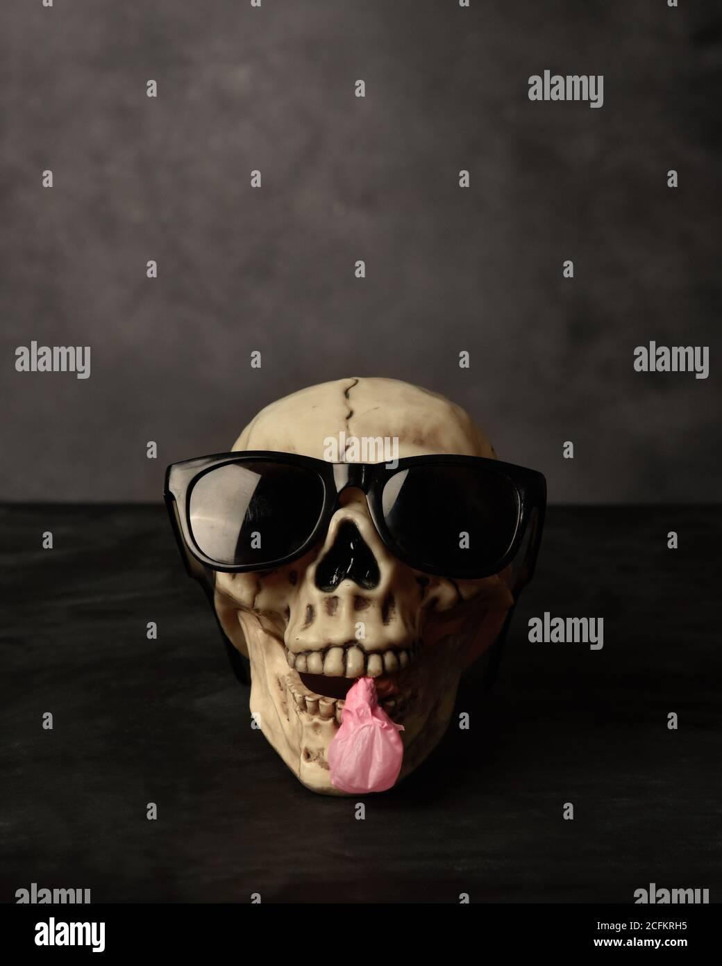Une prop d'halloween de crâne porte des lunettes de soleil avec une bulle de gomme dans la bouche pour un concept festif de fête saisonnière. Banque D'Images
