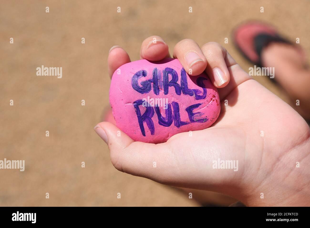 Un enfant tient un rocher rose peint qui dit que les filles règle en lettres pourpres pour un concept de pouvoir de fille d'estime de soi. Banque D'Images