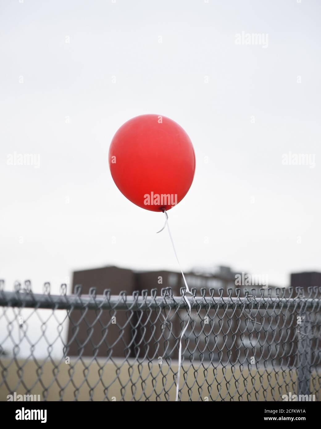 Un ballon rouge est attaché à une clôture en chaîne à l'extérieur pour un concept de solitude ou de solitude. Banque D'Images