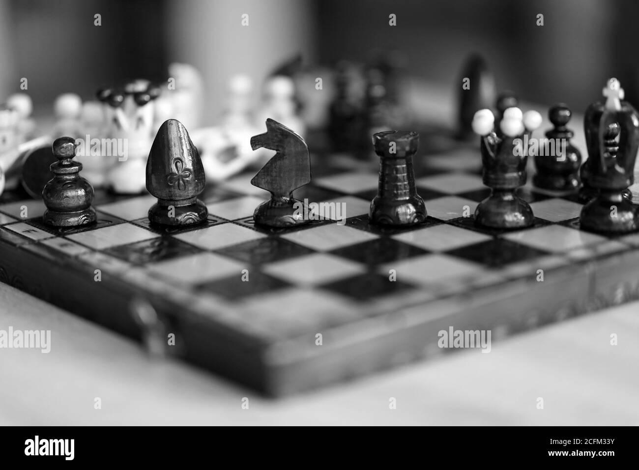 Pièces d'échecs sur plateau de jeu en bois de couleur noire et blanche. Les pièces comprennent le pion, le roi, la reine, l'évêque, le chevalier et le rook. Banque D'Images