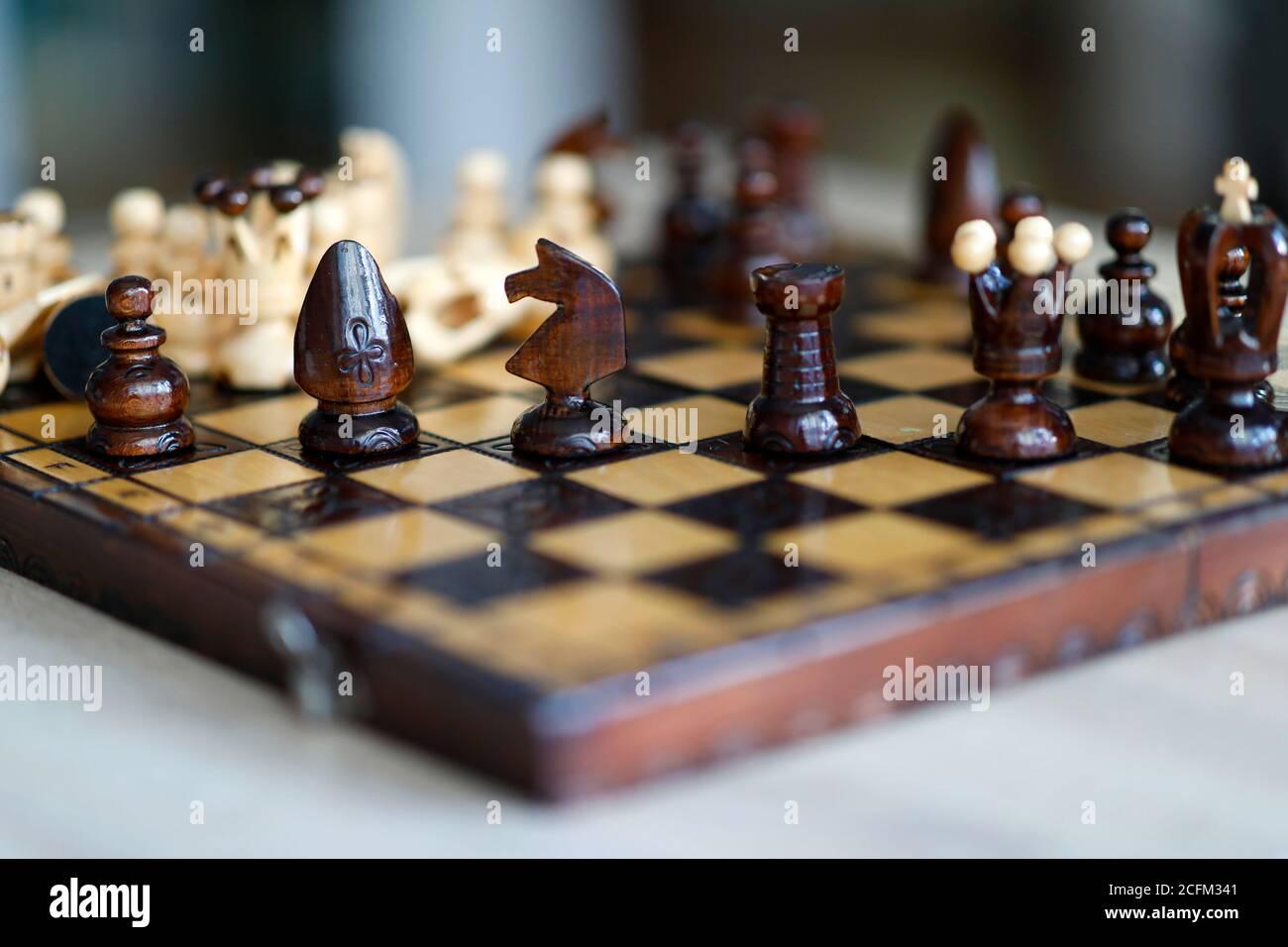 Pièces d'échecs sur une table de jeu en bois. Les pièces comprennent le pion, le roi, la reine, l'évêque, le chevalier et le rook Banque D'Images