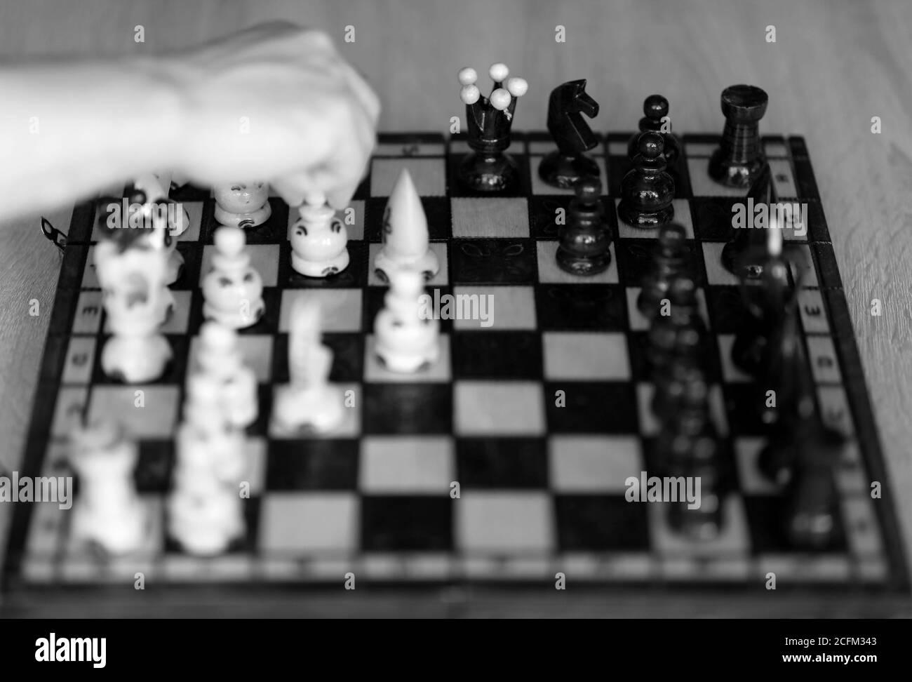 Main du joueur d'échecs dans la décision couleur noir et blanc. Banque D'Images