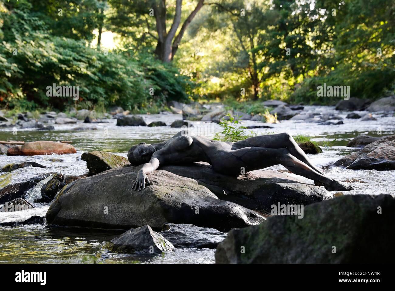 Nature Art: Pierre dans la rivière bodypainting et photoshooting avec le modèle Daniela sur une pierre dans la rivière Chemnitz à Schweizerthal le 6 septembre 2020 - Bodypainting artiste: Joerg Duesterwald Banque D'Images