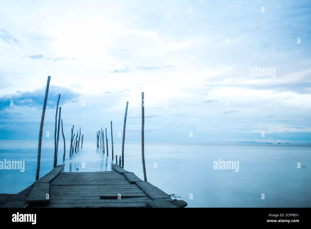 Photographie en longue exposition d'un pont en bois dans la mer bleue Banque D'Images
