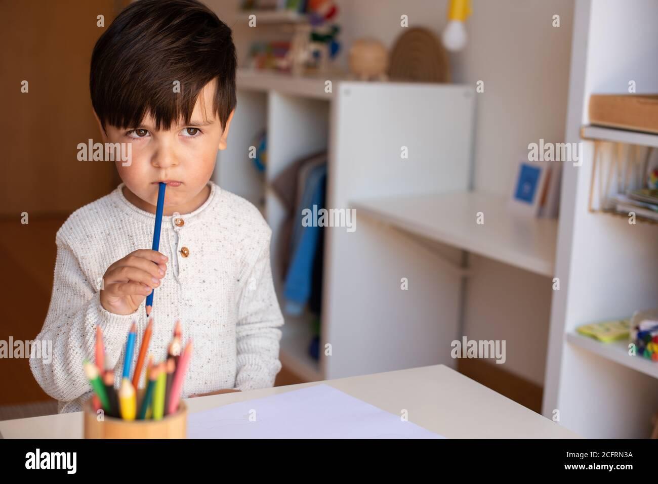 Petit dessin enfant de pré-chooler avec crayons de couleur. Homeschooling. Communauté d'apprentissage. École Montessori. Banque D'Images