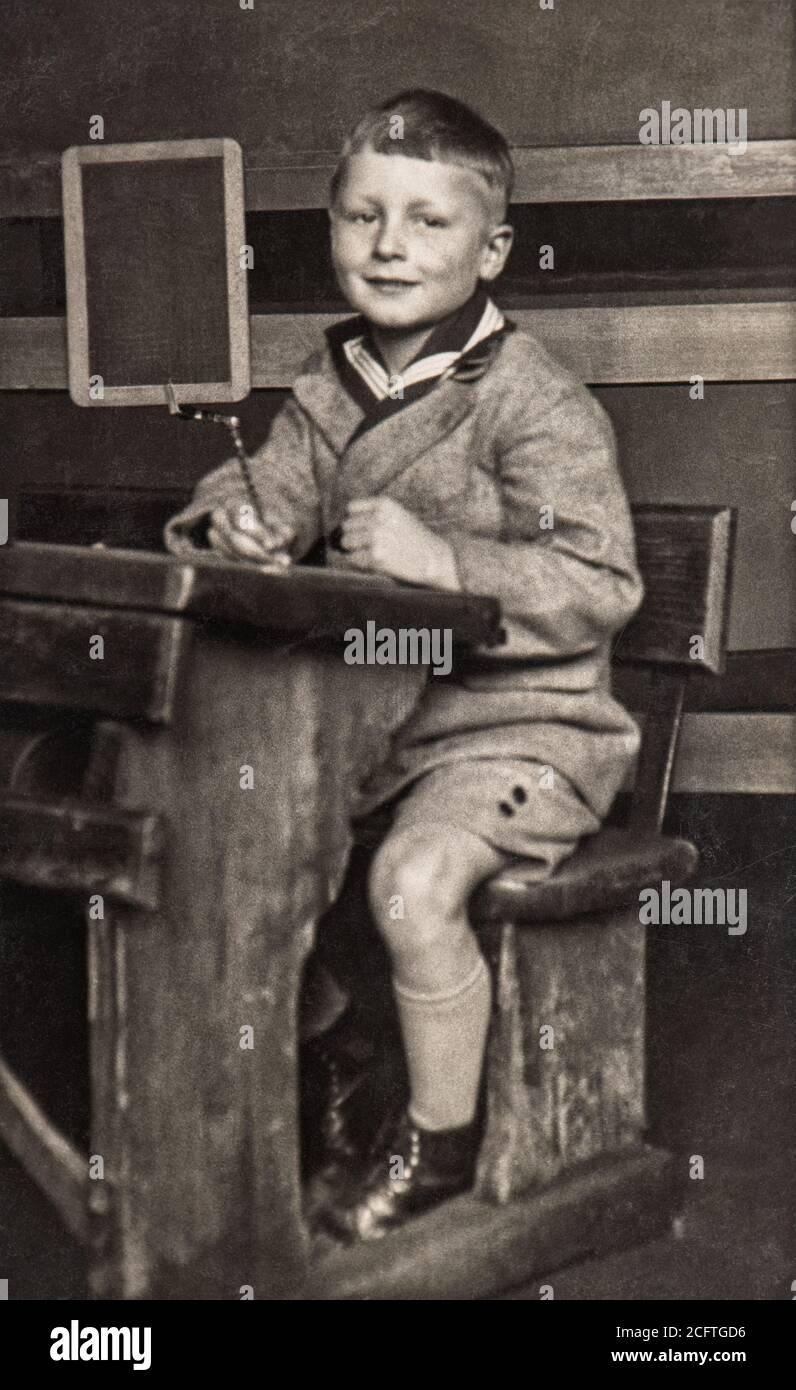 Garçon d'école dans la salle de classe. Photo vintage avec grain original, flou et rayures de env. 1939 Banque D'Images
