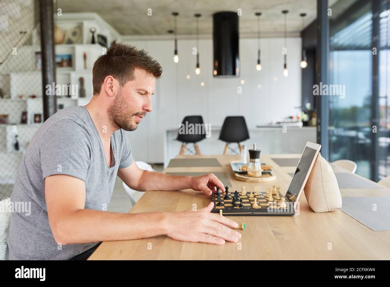 Jeune homme jouant aux échecs dans chat vidéo en ligne à la maison dans le salon Banque D'Images