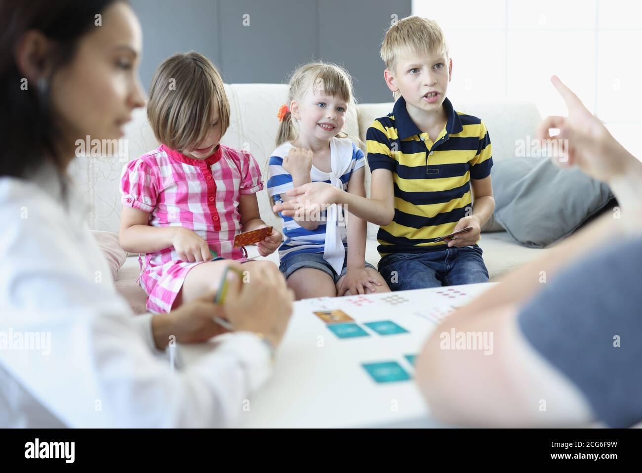 Les adultes et les enfants s'assoient autour d'une table sur laquelle les cartes à jouer sont placées, soutient garçon et discute des règles avec un adulte. Banque D'Images