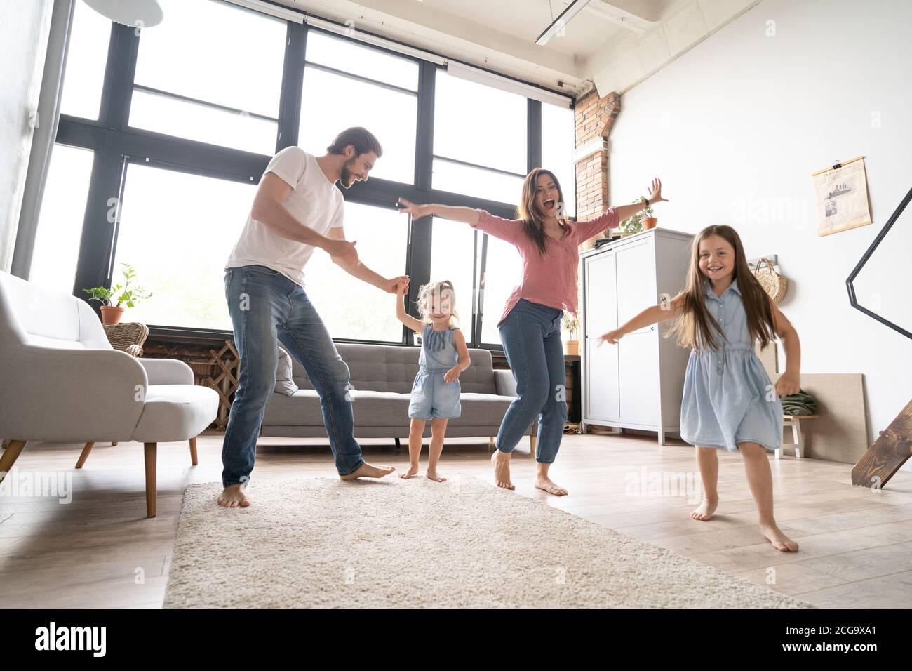 bonne famille mère père et enfant fille dansant à la maison. Banque D'Images