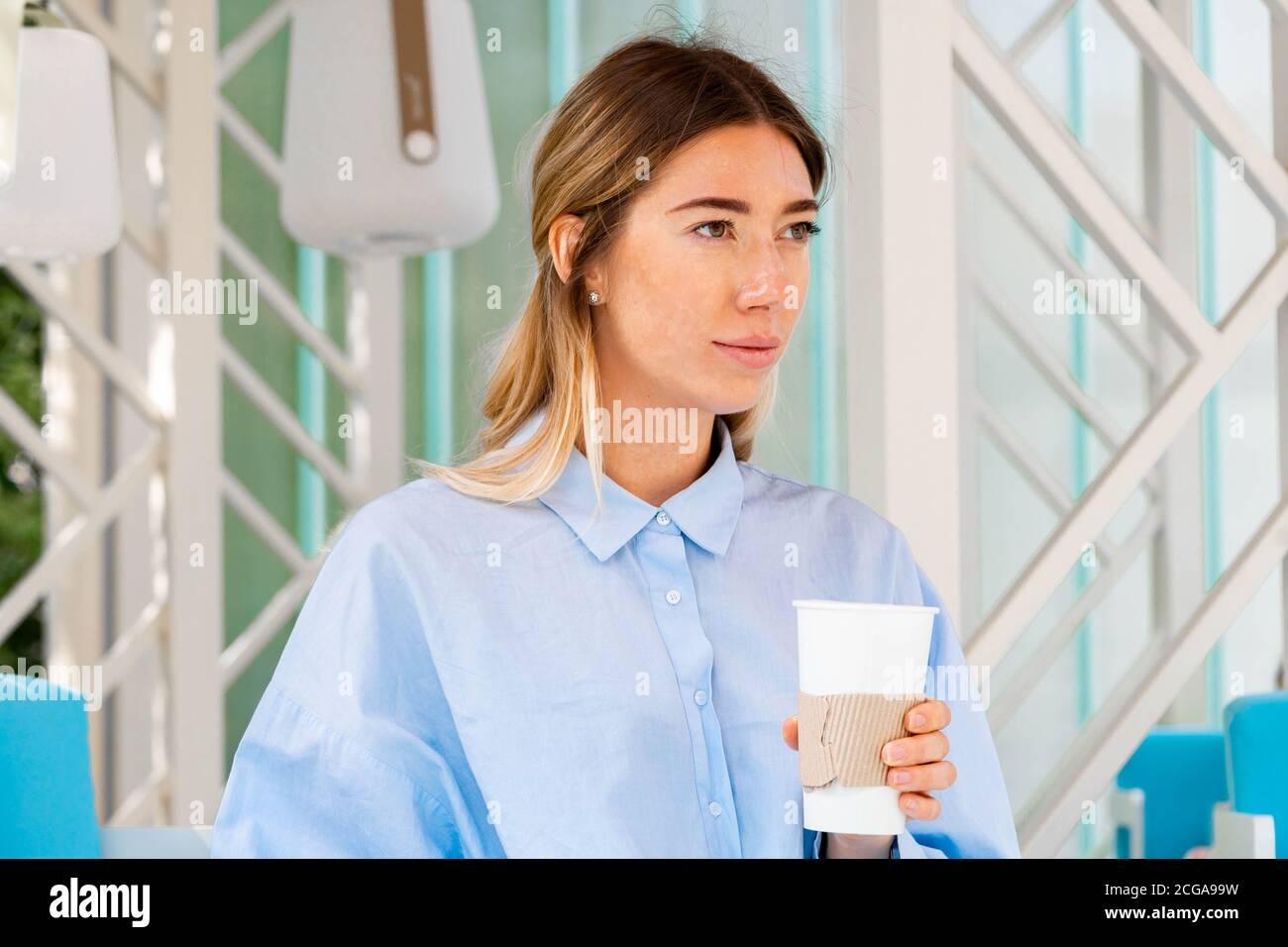 Belle femme buvant du café de café en carton recyclable Takeaway Cup au Street Cafe. Mug avec espace de copie. Espace vide. Banque D'Images