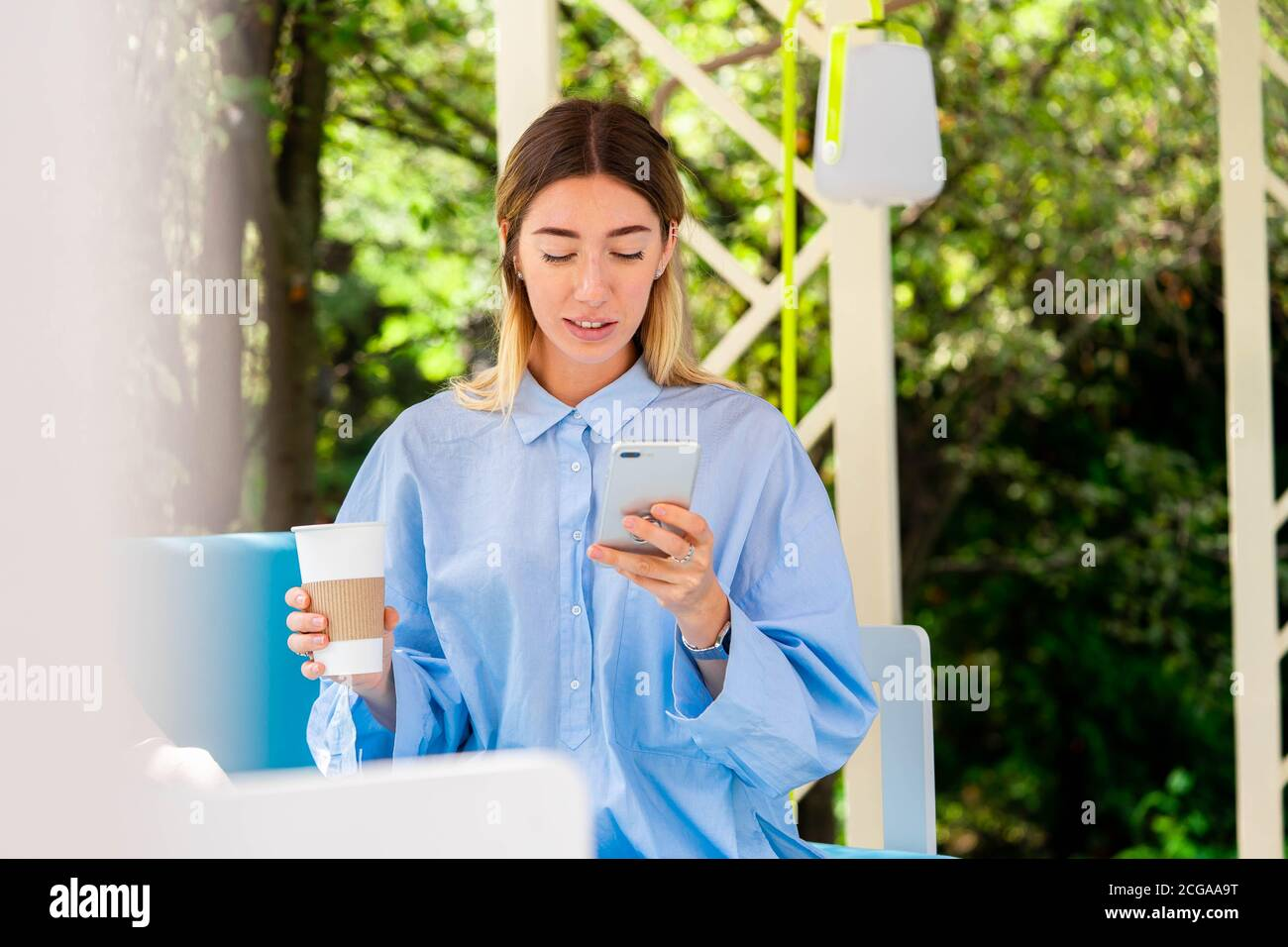 Belle femme buvant du café en carton recyclable Takeaway Cup à Street Cafe et bavarder à Messenger sur Mobile Phone Banque D'Images