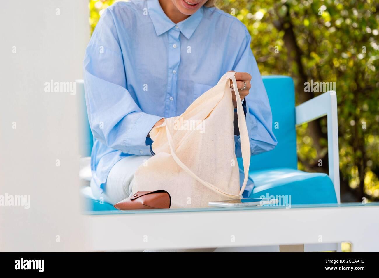 Gros plan sur une femme mettant son téléphone portable dans un sac blanc biodégradable en coton. Produits écologiques. Copier l'espace. Espace vide Banque D'Images