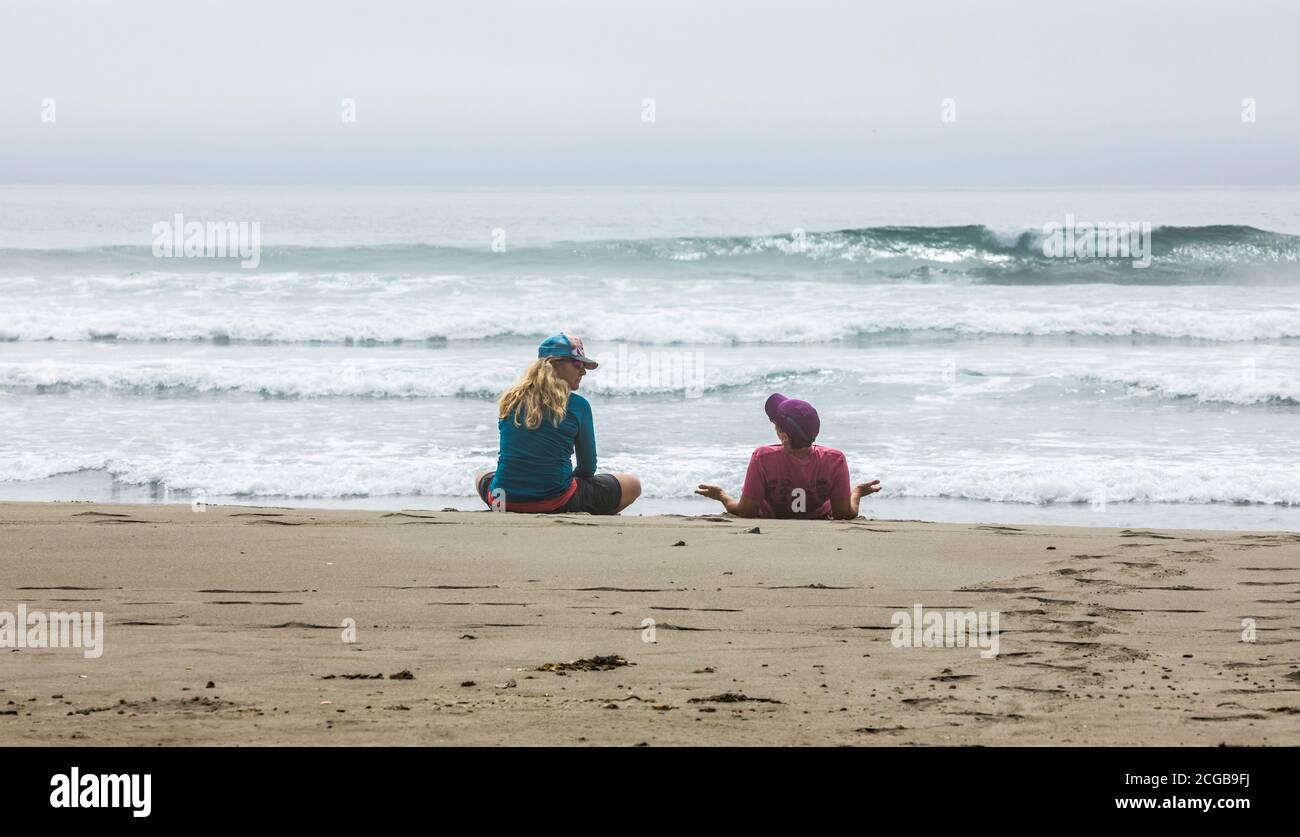 Deux femmes se détendent et parlent sur la plage, la 2e plage, le parc national olympique et le sanctuaire marin national de la côte olympique. Banque D'Images