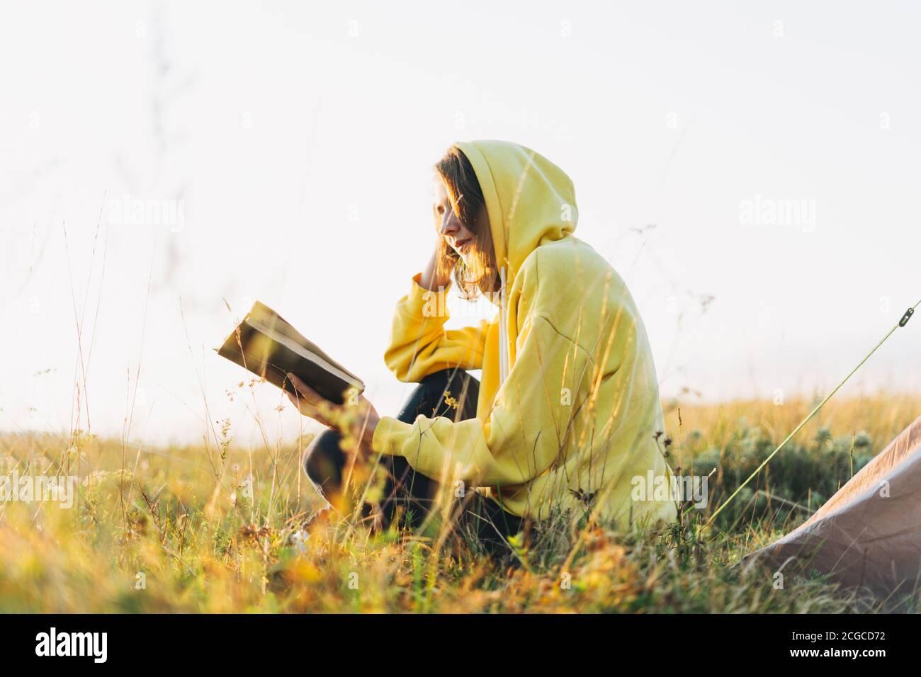 Jeune femme voyageur à capuchon jaune lisant le livre contre la tente. Tourisme local, week-end Banque D'Images