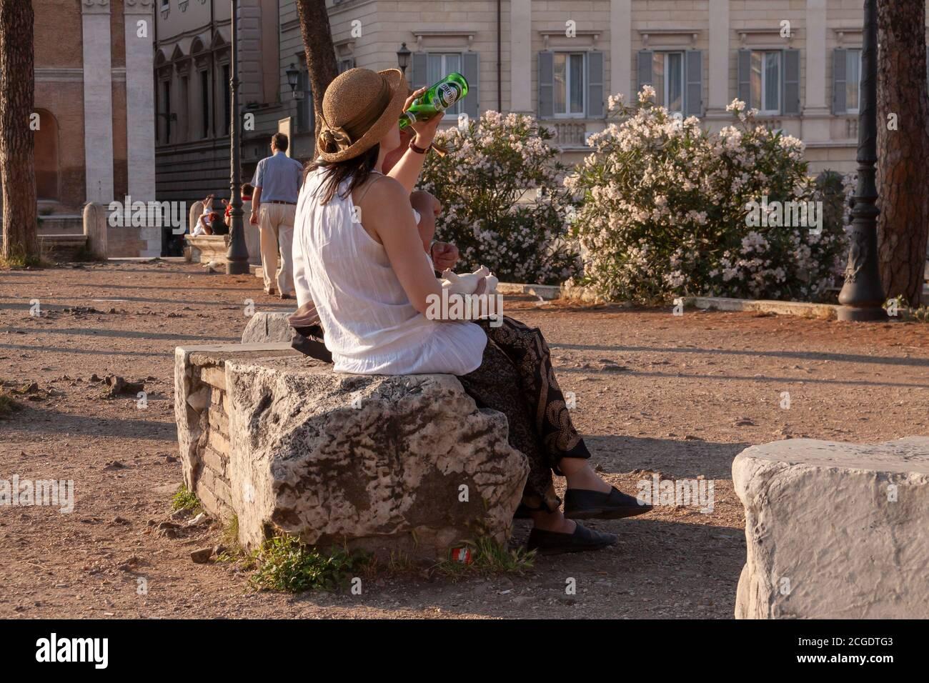 Rome, Italie - 27 juin 2010 : une touriste, portant un chapeau, repose sur un bloc de pierre, buvant une bière, dans la région du Forum romain, Rome. Banque D'Images