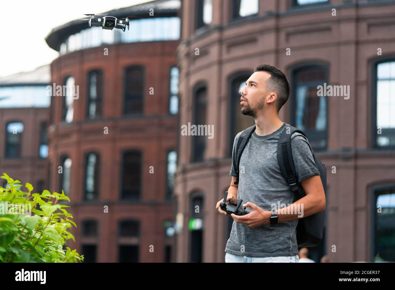 Jeune homme beau qui lance Drone Quadcopter et le regarde. Urbain Stlilysh Paysage urbain contemporain. Appareil moderne Banque D'Images