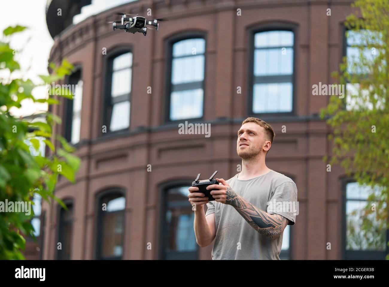 Attrayant tatoué homme de lancement de Drone Quadcopter et le regardant. Le bâtiment rouge élégant est situé en arrière-plan. Appareil moderne Banque D'Images