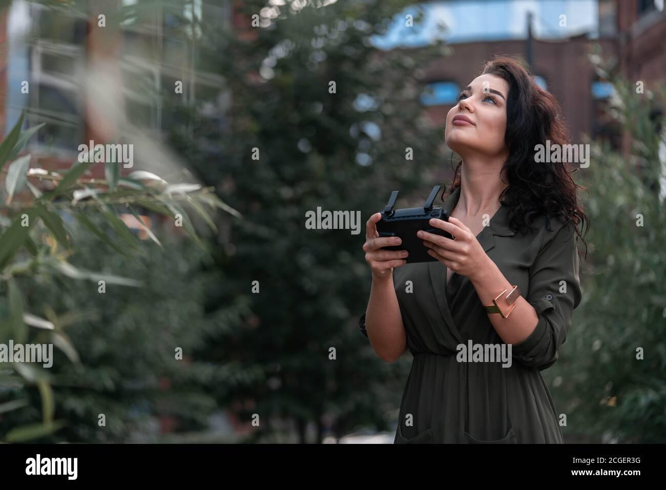 Jeune belle femme lançant Drone Quadcopter à Modern Park et regardant Sky. Vidéographie. Appareil moderne. Banque D'Images