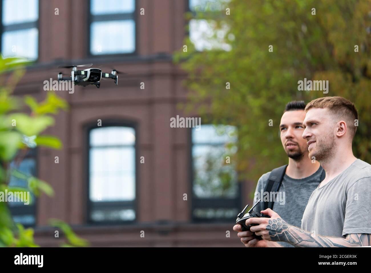 Deux jeunes hommes séduisant lancent Drone Quadcopter à Urban Stlilysh Contemporary Cityscape. Appareil moderne Banque D'Images