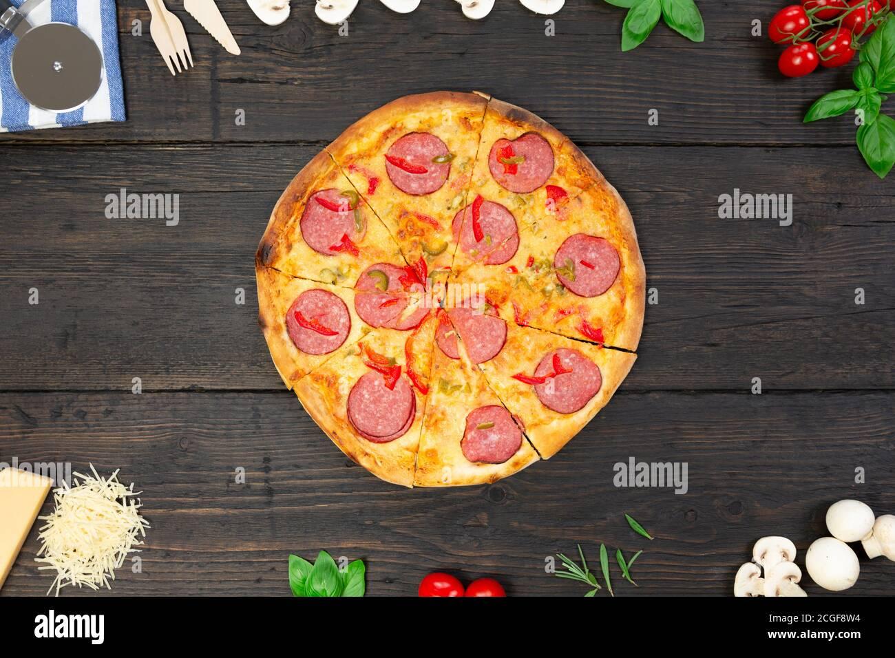 Savoureuse pizza chaude avec des ingrédients et un couteau à pizza sur fond de texture noire. Vue de dessus Banque D'Images