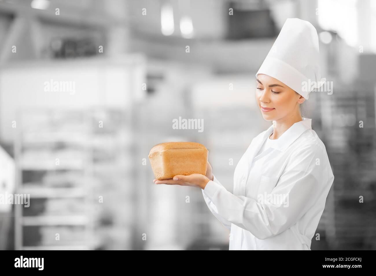 Femme boulangère en uniforme blanc tenant le pain de baguette chaud dans les mains à la boulangerie, fond de la chaîne de production alimentaire Banque D'Images