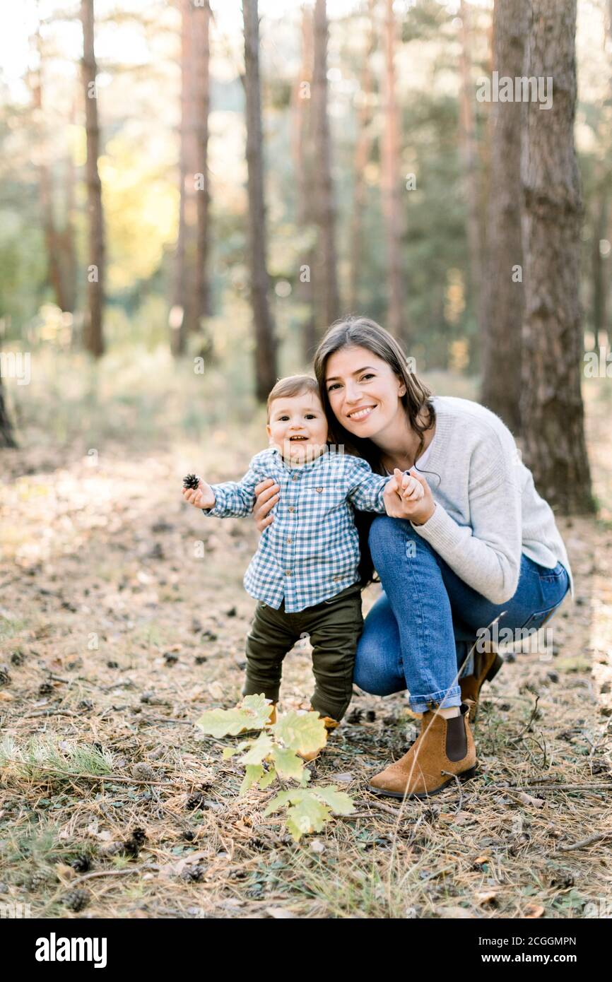Portrait d'automne extérieur de la jeune jolie femme mère posant dans la forêt de pins d'automne avec son joli petit fils mignon, riant ensemble. Banque D'Images