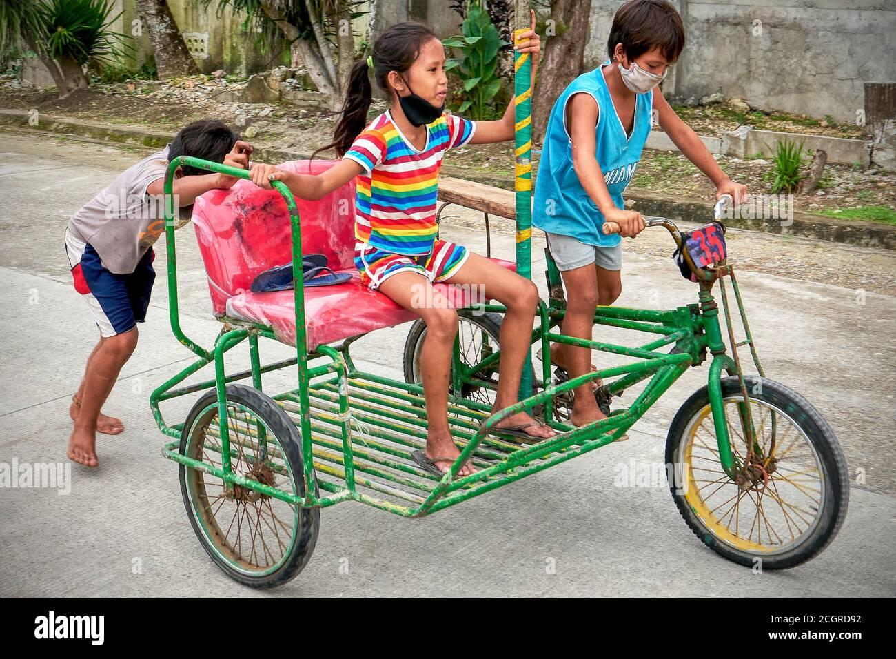 Trois jeunes enfants barefootés portant un masque de visage sur un pédicab peint traditionnel coloré sur une route sur l'île de Boracay, Philippines, Asie Banque D'Images