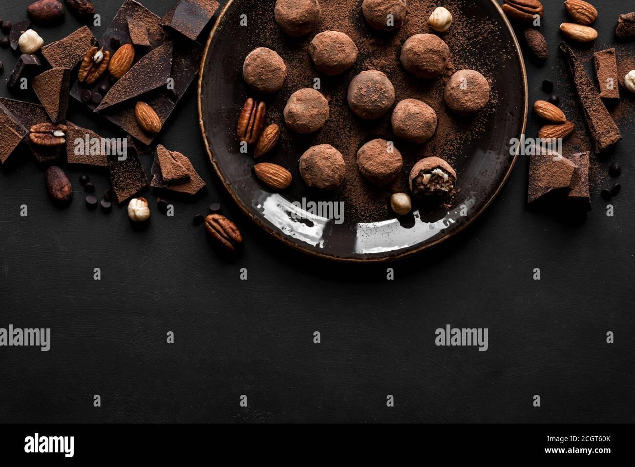 Truffes au chocolat avec chocolat noir et noix sur fond noir, vue de dessus, espace de copie. Boulettes d'énergie au chocolat maison vegan ou truffes pour le desse Banque D'Images