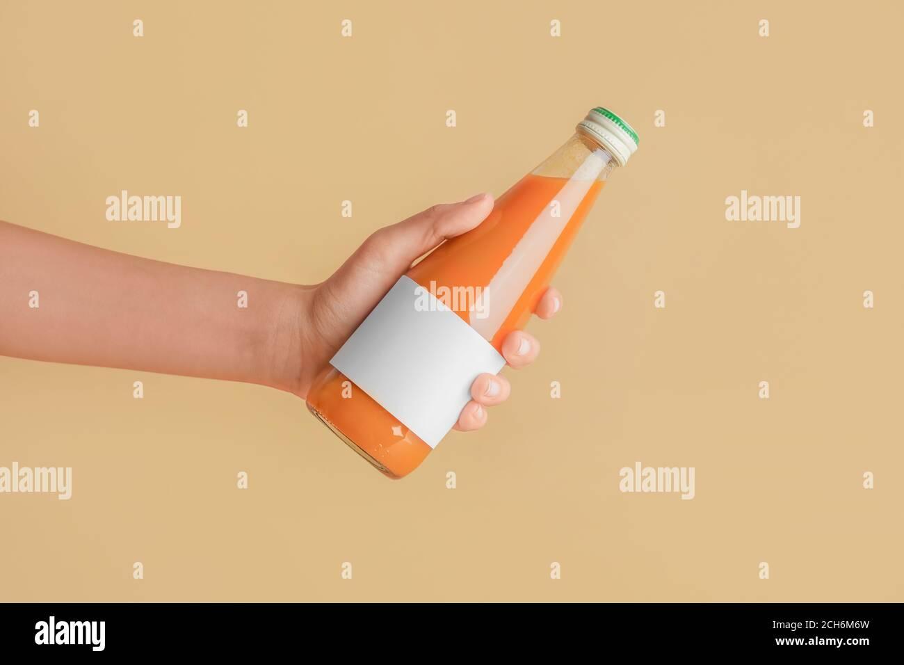 Main femelle avec bouteille de jus sur fond de couleur Banque D'Images