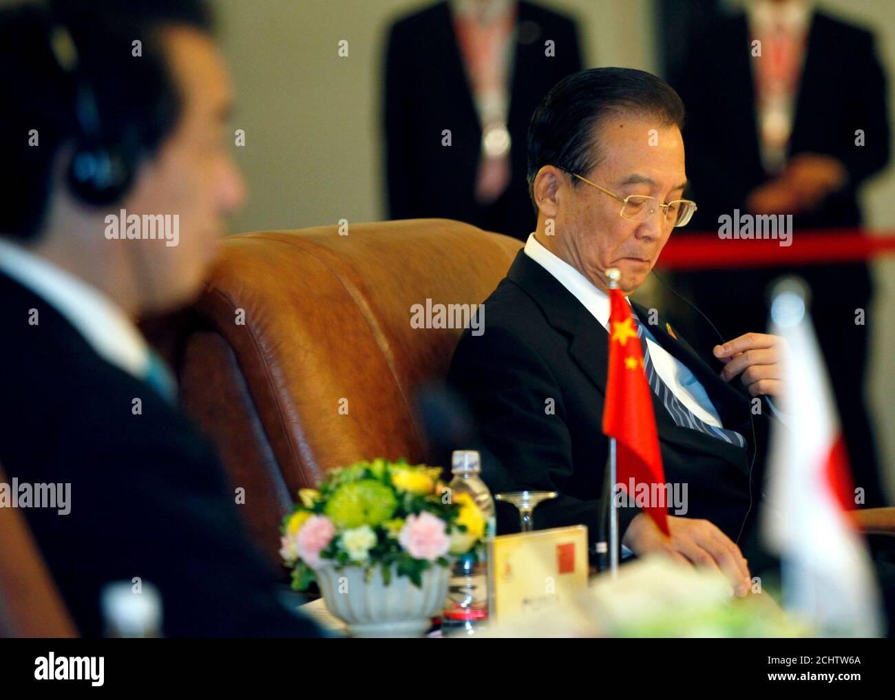 Le Premier ministre chinois Wen Jiabao (R) ajuste ses écouteurs alors que le Premier ministre japonais Naoto Kan se trouve à côté de lui lors du 13ème Sommet ASEAN plus trois, en marge du 17ème Sommet de l'ANASE à Hanoï le 29 octobre 2010. Les liens entre la Chine et le Japon se sont détériorés le mois dernier après la détention d'un capitaine de bateau de pêche chinois par la garde côtière japonaise après la collision de leurs bateaux près d'îles contestées en mer de Chine orientale. REUTERS/Damir Sagolj (VIETNAM - Tags: POLITIQUE) Banque D'Images