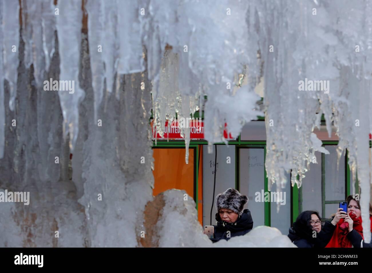 Une femme s'arrête pour photographier la Fontaine commémorative Josephine Shaw Lowell, gelée, à New York, aux États-Unis, le 3 janvier 2018. REUTERS/Lucas Jackson Banque D'Images