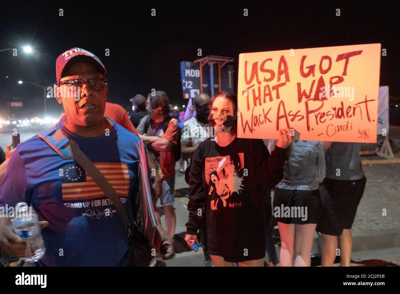 Henderson, NV, États-Unis. 13 septembre 2020. Un partisan du président Donald Trump se défend contre le mouvement Black Live Matter alors qu'un protestataires porte un signe anti-Trump avec une citation de Cardi B à côté de lui. Près de 10 manifestants se sont présentés à la manifestation du président Donald Trump à Henderson, dans le Nevada, en scandant et en tenant des panneaux devant le bâtiment Xtreme Manufacturing où Trump s'exprimait. Crédit : jeunes G. Kim/Alay Live News Banque D'Images