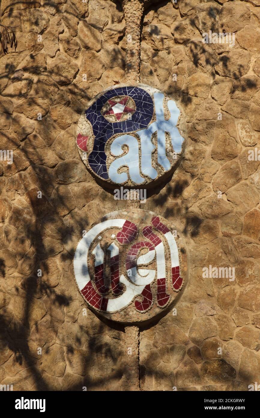 Inscription en mosaïque de Trencadís sur la clôture du Parc Güell conçue par l'architecte moderniste catalan Antoni Gaudí et construite entre 1900 et 1914 à Barcelone, Catalogne, Espagne. Banque D'Images