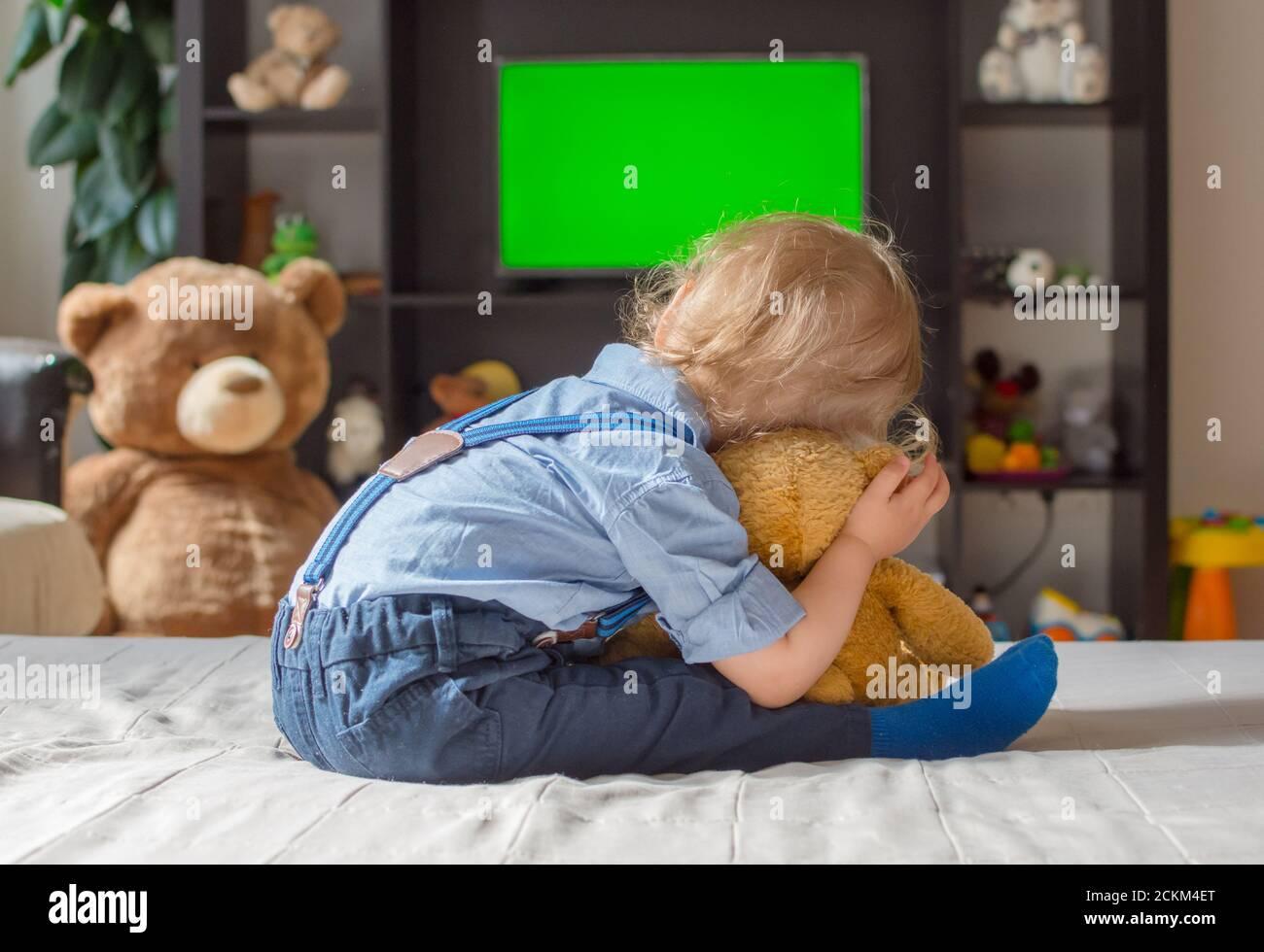 Un joli petit garçon et son ours en peluche regardant la télé s'asseoir sur un canapé dans le salon à la maison Banque D'Images