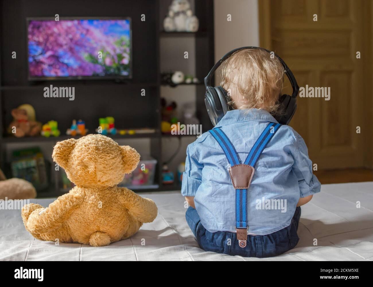 Un joli petit garçon avec un casque et son ours en peluche Téléviseur assis sur un canapé dans le salon à accueil Banque D'Images
