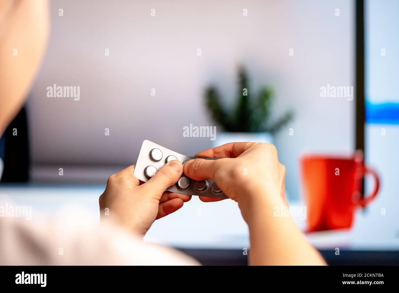 Femme poussant des pilules ou des comprimés de Blister Packaging à l'intérieur moderne de cuisine lumineuse. Prise Painkiller, antibiotique, médicament, placebo Banque D'Images