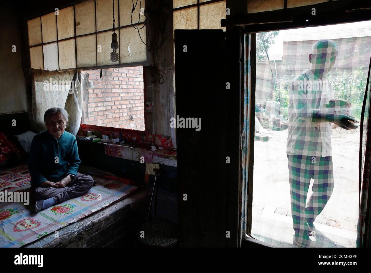 L'ancienne 'femme de confort' chinoise Zhang Xiantu repose sur un lit traditionnel en brique tandis que son fils apporte son déjeuner à Xiyan Town, province du Shanxi, Chine, le 18 juillet 2015. « les femmes de confort » est l'euphémisme japonais pour les femmes qui ont été forcées à la prostitution et victimes d'abus sexuels dans des maisons de prostitution militaires japonaises avant et pendant la Seconde Guerre mondiale. Zhang est la seule ancienne 'femme de réconfort' survivante des 16 plaignants de Shanxi qui ont poursuivi le gouvernement japonais en 1995 pour avoir enlevé des filles et les utiliser comme 'femme de réconfort' pendant la deuxième Guerre mondiale. Selon les informations de la Commission d'enquête de la Chine sur le fait Banque D'Images