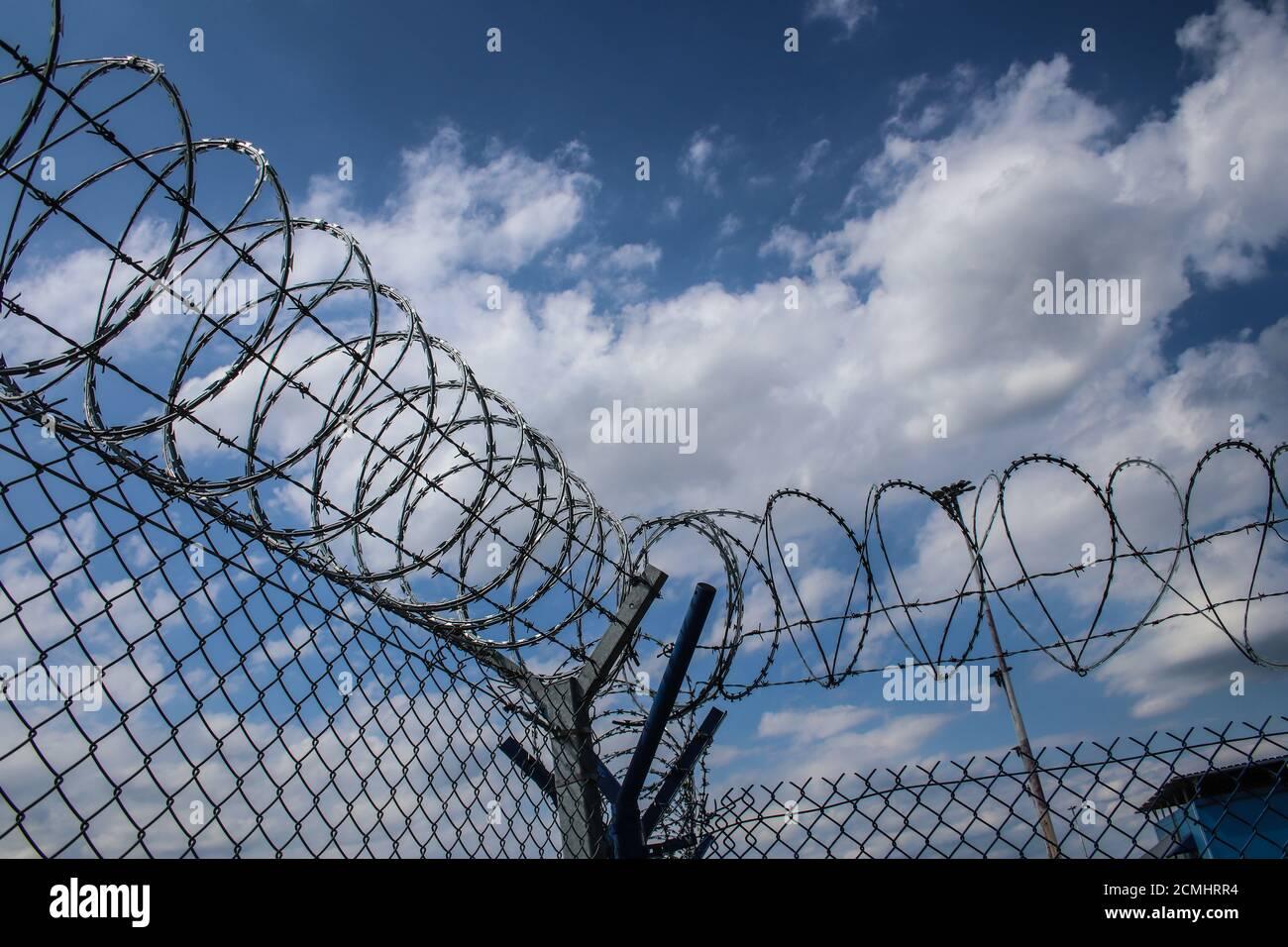 Fil barbelé sur le dessus de la clôture de filet métallique aéroport contre ciel nuageux Banque D'Images