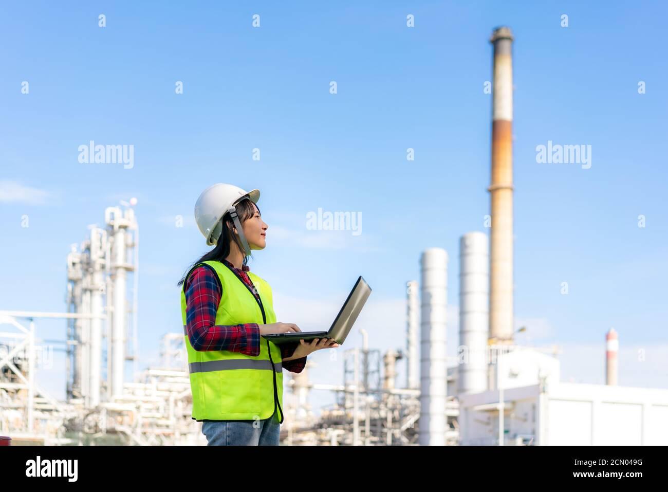 Femme asiatique ingénieur pétrochimique travaillant la nuit avec un ordinateur portable dans l'usine de raffinage de pétrole et de gaz la nuit pour la sécurité des inspecteurs Banque D'Images