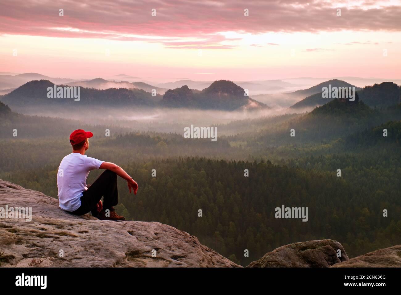 Adulte sportif en chemise blanche, troussards foncés et casquette rouge. Ginger Short Hair man s'asseoir sur une falaise vive au-dessus de la vallée dans la montagne rocheuse Banque D'Images