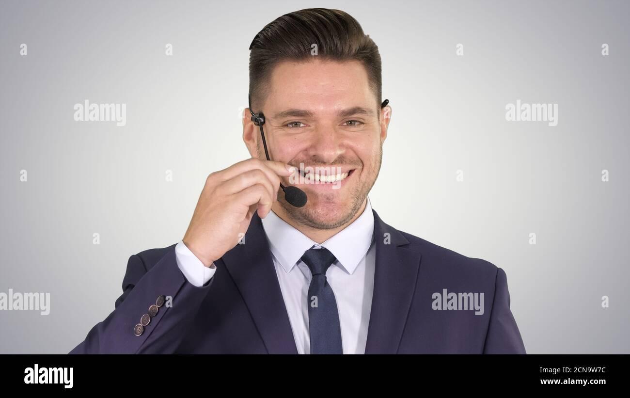 Un homme d'affaires charmant avec un micro-casque qui regarde dans l'appareil photo et le smilin Banque D'Images