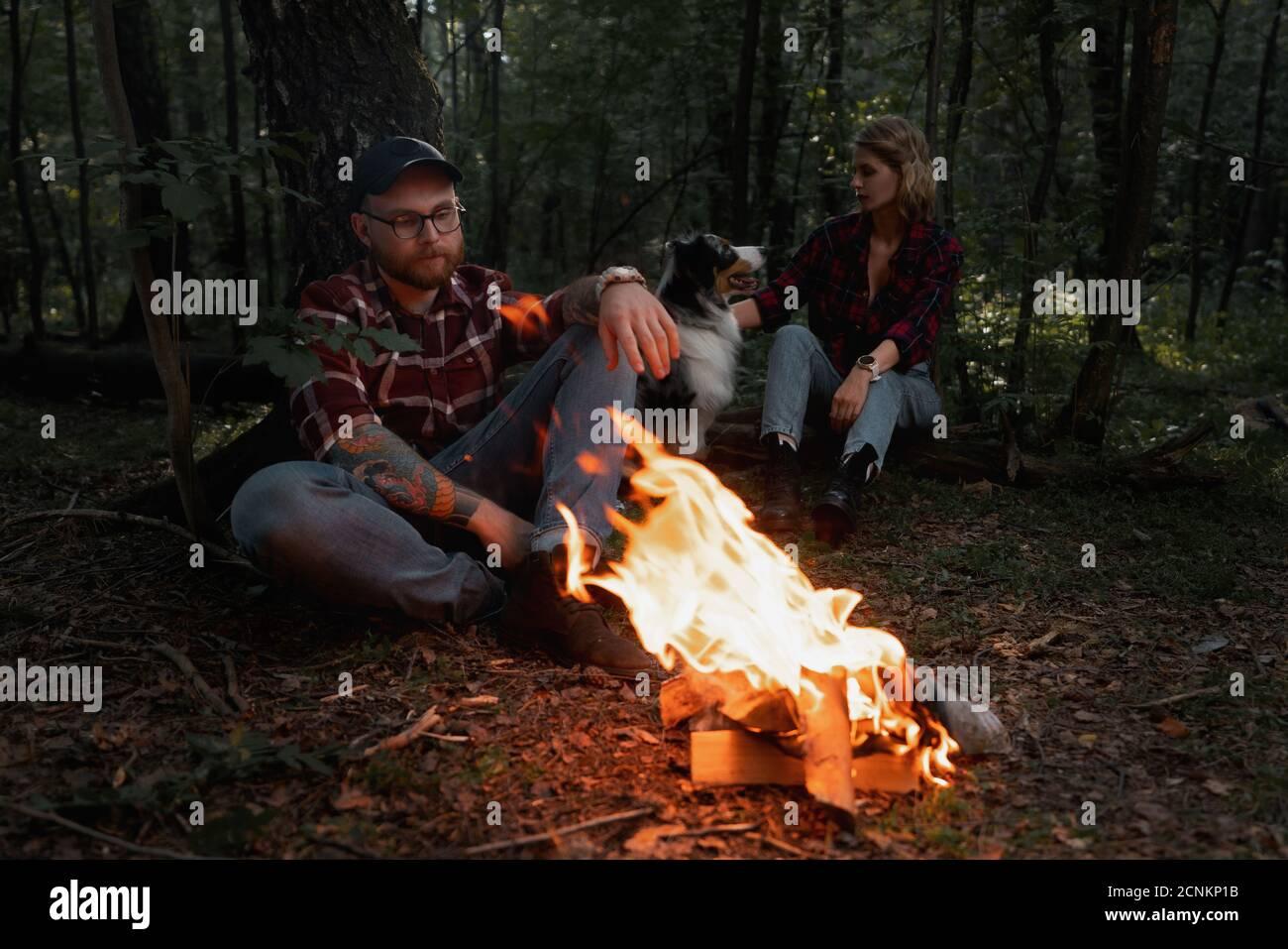 Belle Backpacker femme et homme ayant le repos près de Bonfire après se promener et randonnée dans la forêt avec Aussie chien de race australienne. Contient du chrominanc Banque D'Images