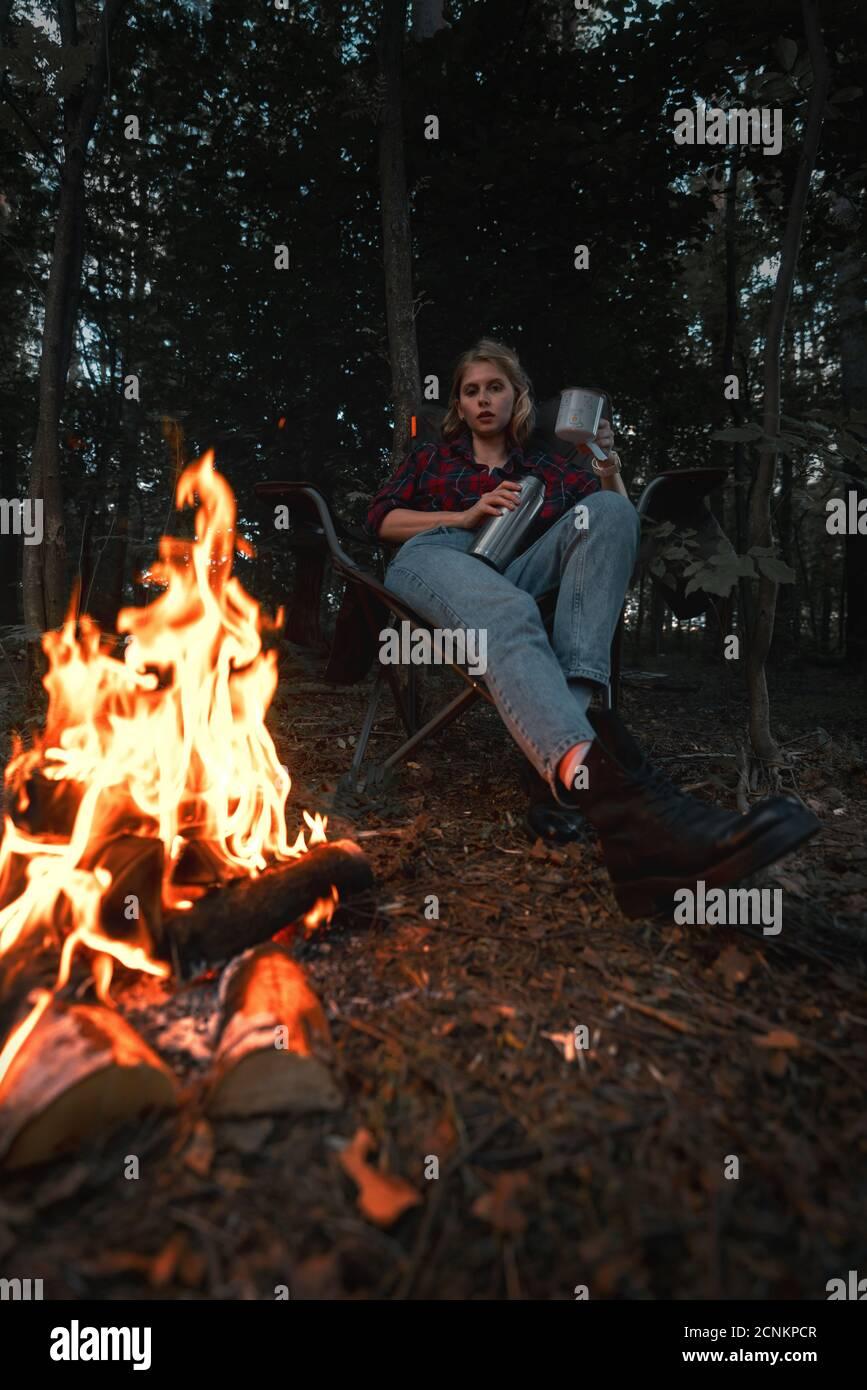 Belle femme de randonnée ayant le repos près de Bonfire après se promener et randonnée dans la forêt et verser le thé dans la tasse métallique de Thermos. Contient de la chrominance Banque D'Images