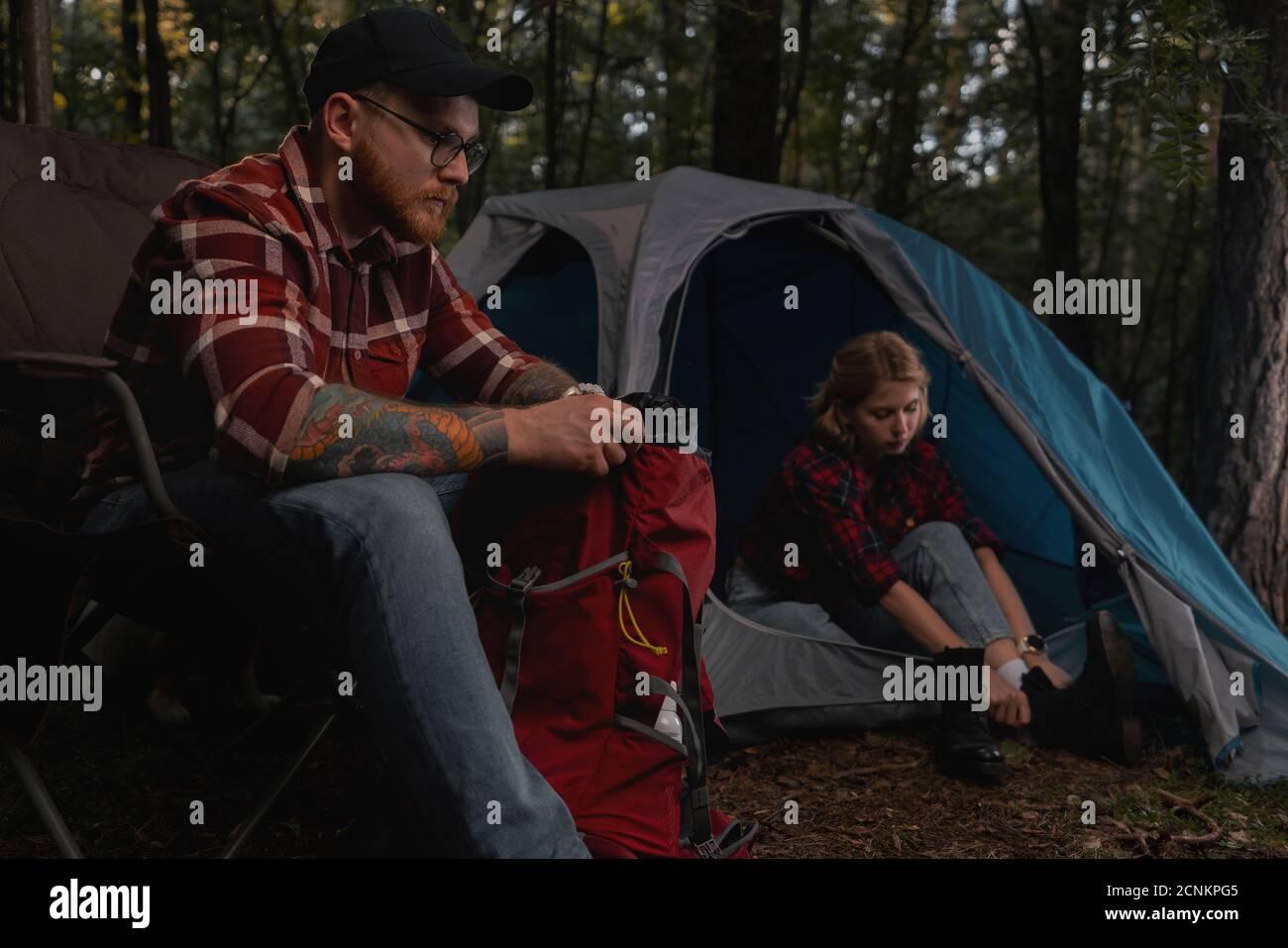 Couple de randonnée tirant la tente et tirant les choses hors de sac à dos. Histoire d'amour dans la forêt au paysage naturel, contient bruit de chrominance, luminance Banque D'Images