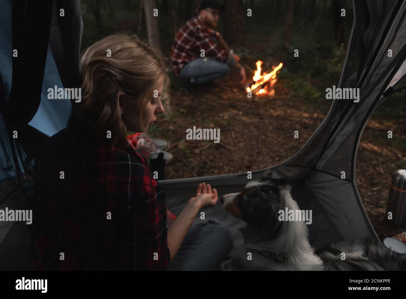 Femme et chien Aussie assis dans une tente, Hipster Bearded Man près de Bonfire hors de la tente dans la Forêt automnale sombre. Voyage à Native Coutry, vacances Banque D'Images