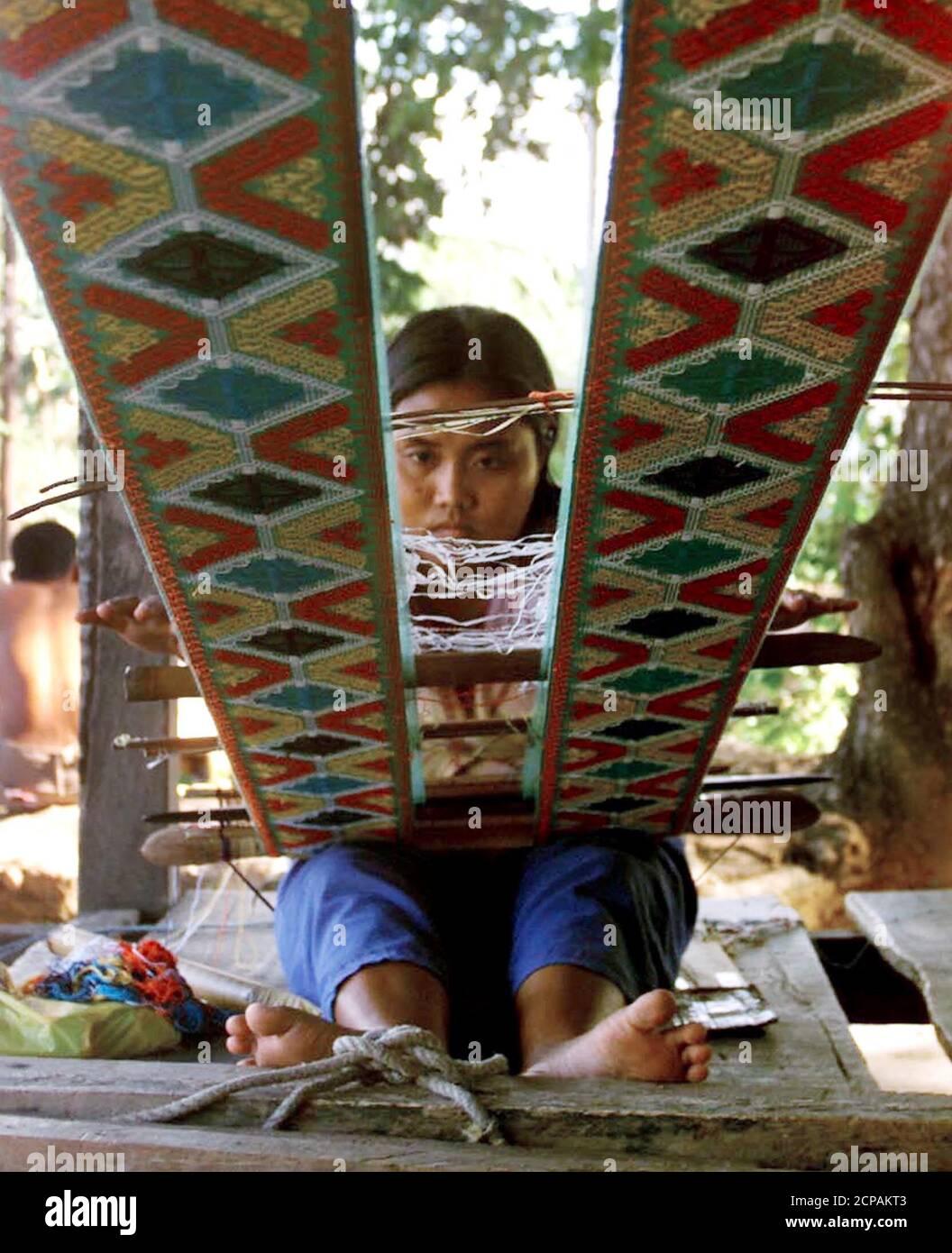 """La tribesfemme philippine Ida Jamaani, 20 ans, délasse un tissu Yakan pour servir de taupe de prêtre au village de tissage Yakan dans la ville de Zamboanga, dans le sud des Philippines le 1er août 2000. Le village de tissage de Yakan a été une attraction touristique à Zamboanga, populaire pour ses tissus, mais le propriétaire dit """"que l'enlèvement de touristes rampant dans toute Mindanao a coûté une vente à faible profit"""". Au moins 29 ressortissants étrangers pour la plupart sont encore pris en otage par le extrémiste musulman Abu Sayyaf dans leur cachette de Patikul, île de Sulu, dans le sud des Philippines. RR/HL Banque D'Images"""