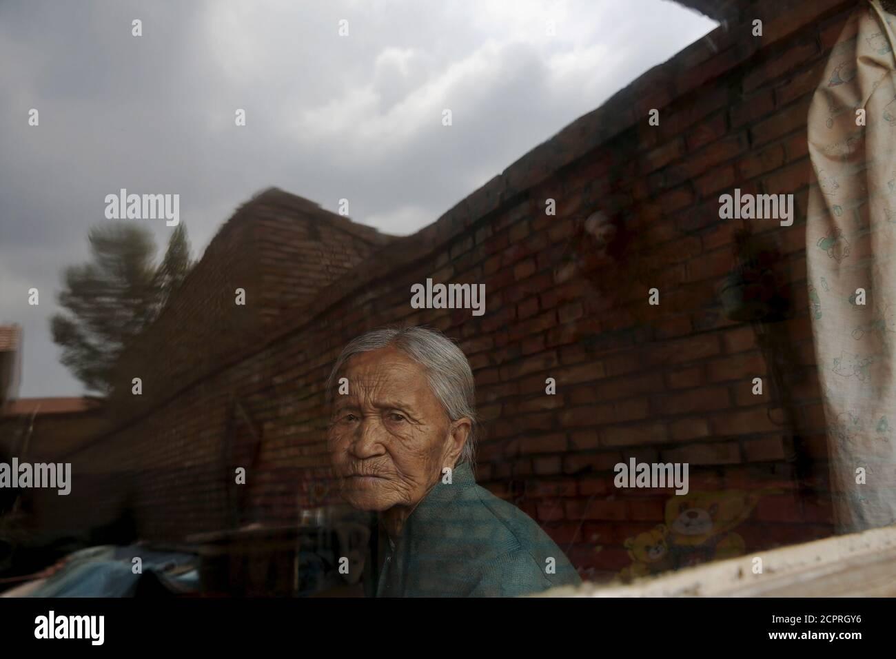 L'ancienne 'femme de confort' chinoise Zhang Xiantu regarde par la fenêtre de sa maison dans la ville de Xiyan, province du Shanxi, Chine, le 18 juillet 2015. € œComfort femme? Est l'euphémisme japonais pour les femmes qui ont été forcées à la prostitution et victimes d'abus sexuels dans des maisons de prostitution militaires japonaises avant et pendant la Seconde Guerre mondiale. Zhang Xiantu est la seule 'femme de réconfort' survivante des 16 plaignants du Shanxi qui ont poursuivi le gouvernement japonais en 1995 pour avoir enlevé des filles et les utiliser comme 'femme de réconfort' pendant la deuxième Guerre mondiale. Selon les renseignements de la Commission d'enquête de China sur les faits de Comfort Wome Banque D'Images