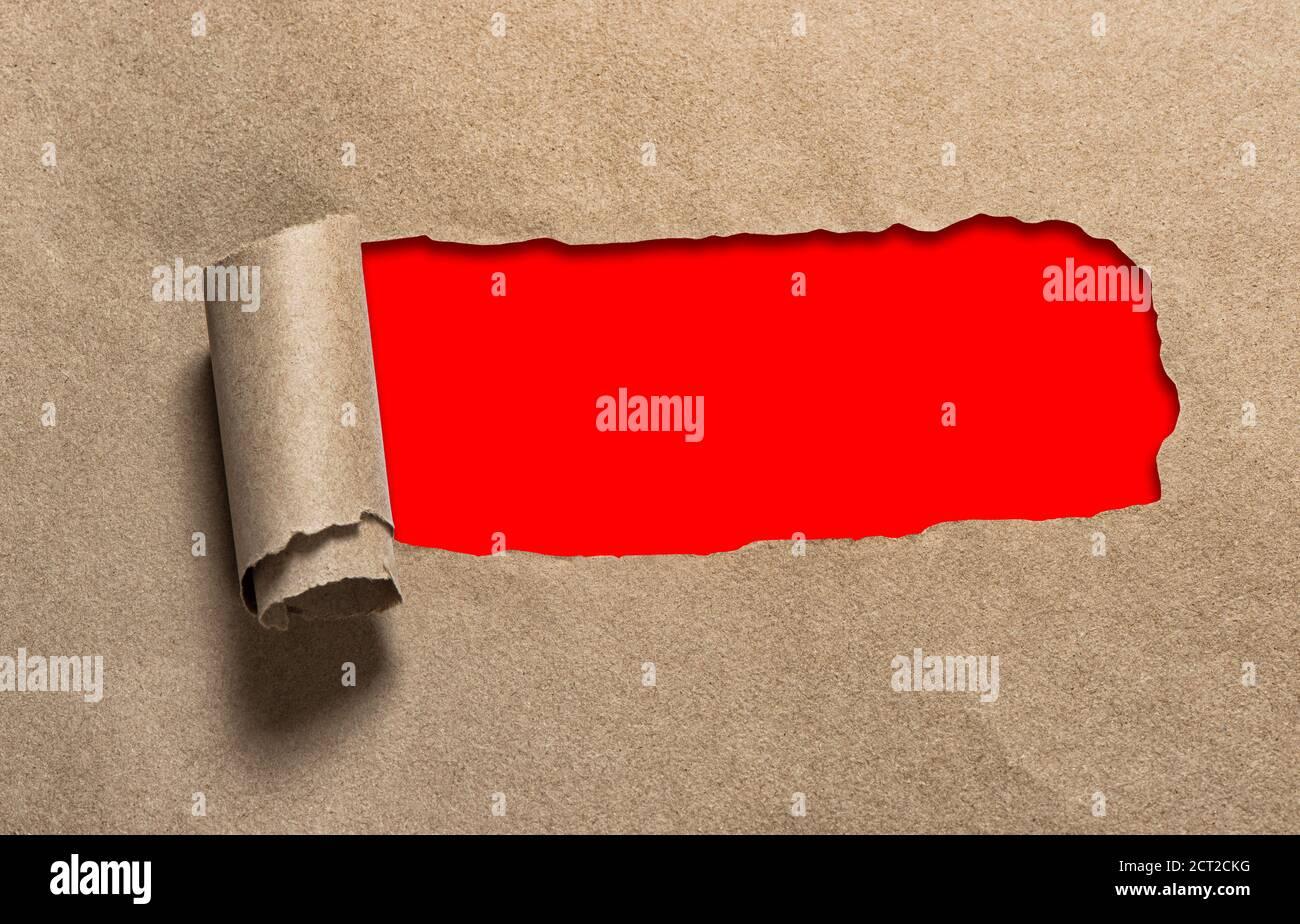 Trou déchiré dans le papier artisanal avec espace de copie rouge Banque D'Images