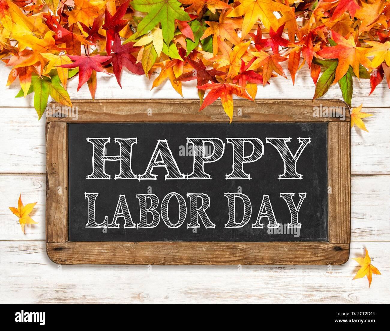 Bonne journée du travail. Feuilles d'automne et tableau noir sur fond de bois clair Banque D'Images